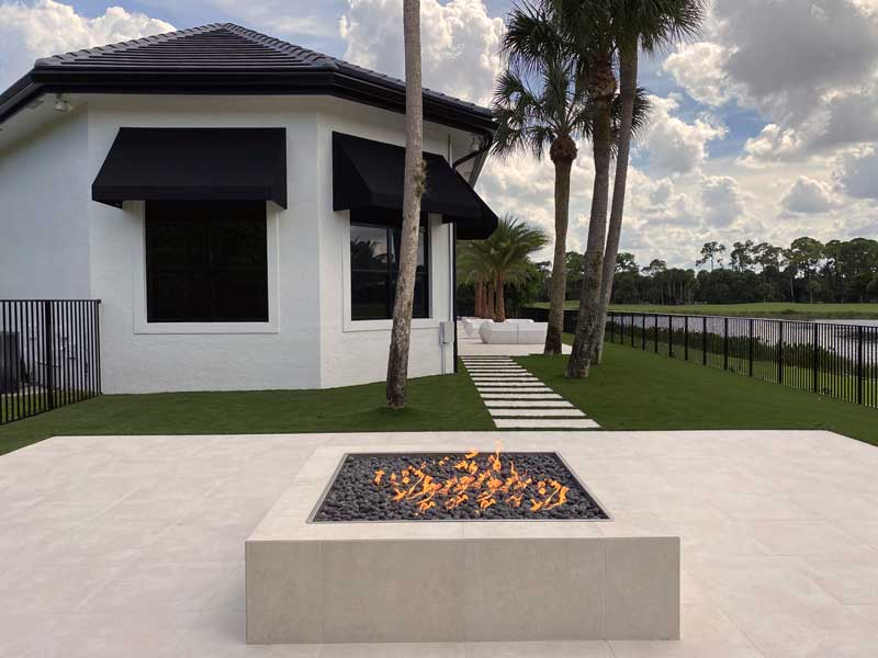 hardscape project with fireplace and patio overlooking water